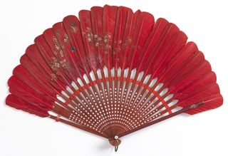 Brisé fan. Red feathers painted with a bird and flowers mounted on wood sticks painted red and stamped with silver stars. Red silk connecting ribbon. Metal bail ring and bone washer at rivet.