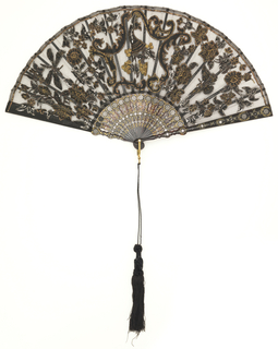 Pleated fan. Black net leaf with applied silk panels in the form of scrolls, flowers and butterflies, and spangles of varying shapes. Carved and gilded tortoise shell sticks inlaid with steel piqués. Gilt metal bail and white stone at rivet. Black silk tassel.