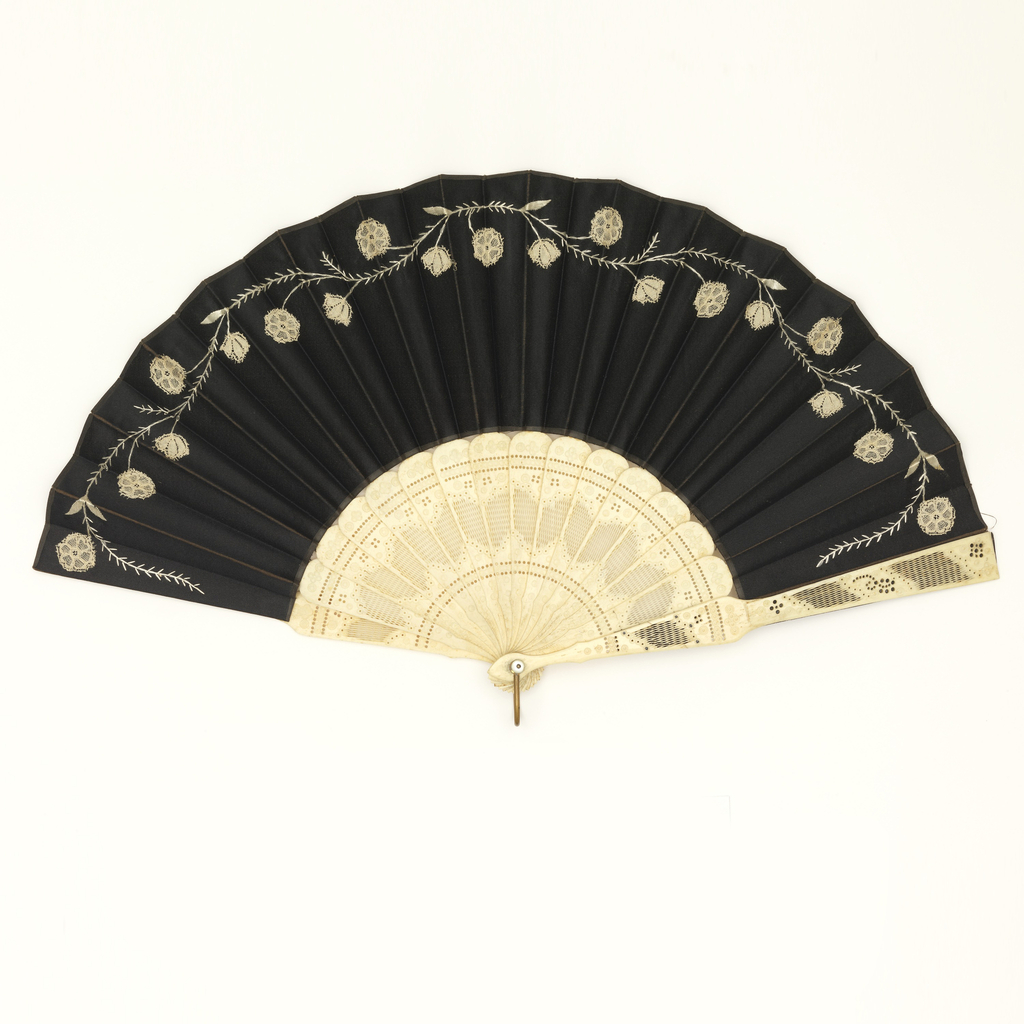Pleated fan with a black silk leaf with a simple meandering floral vine embroidered with white silk and appliquéd with white machine made lace flowers. Drilled and pierced bone sticks. Mother-of-pearl washer and metal loop at the rivet.
