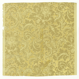 On metallic gold ground, large fantastic flowers with feathered and plume-like leaves in tan and white.