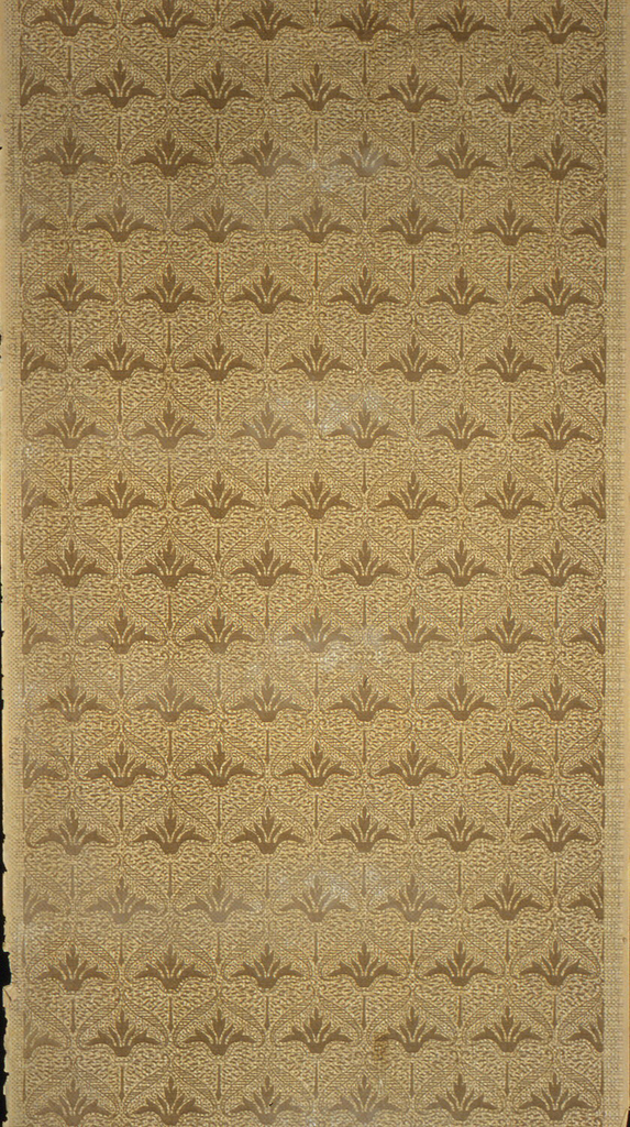 Repeating design of a foliate motif, printed in rows. The motif sits under an ogival arch. Printed in tans and brown on tan ground.