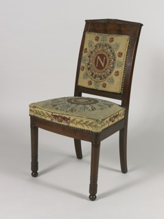 "Chair consists of mahogany frame with thick headpiece that culminates at a central point.  Tapered front and back legs. Front legs terminate in ball feet.  Seat frame curves outwards.  Upholstery on chair back and seat characterized by a buttoned frame.  ""N""-like medallion in needlepoint embroidered into upholstery."