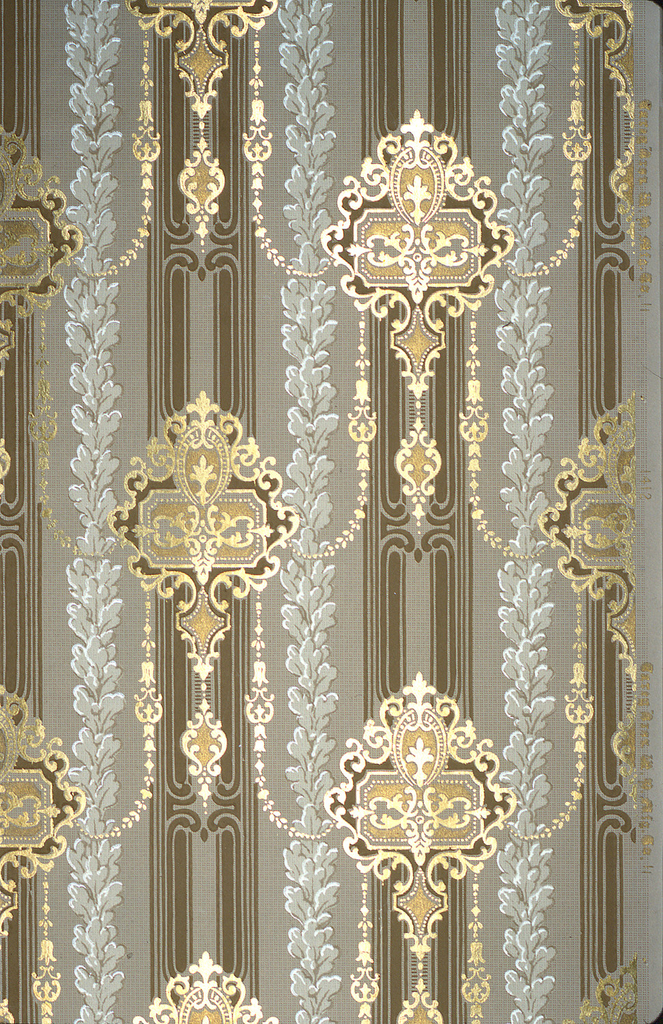 Vertical pattern of dark green-brown bands with staggered gold medallions composed of rectangles bearing scrolls and pendants, all connected by floral chains; long gray floral rinceaux.