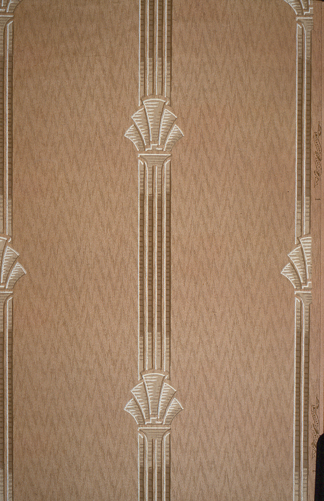 On tan-pink striated ground, vertical fluted bands with fanned motifs in white and tan.