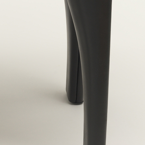 Rectilinear seat and legs surmounted by U-shaped arm/back support rising from central post at back of seat; the whole covered in black leather.