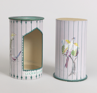 """Prototype for a two-part package consisting of cylindrical sleeve (a) over cylindrical box (b), both parts with painted decoration depicting birds in an aviary or bird cage. Sleeve with green circular top with LeLong logo; cylindrical wall painted with gray ground and green """"bars"""" through which are visible birds with bright multicolored plumage, all on tree-like perches; five-sided opening surrounded by scalloped green border and """"LUCIEN LELONG"""" below, through which the cylindrical box is visible. Box features perched bird with white and multi-colored plumage, wings outstretched; bright green circular base. Sleeve lifts off box."""