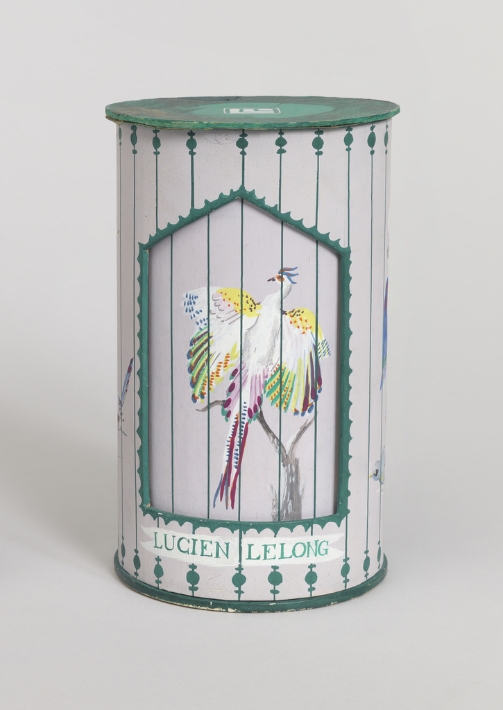 "Prototype for a two-part package consisting of cylindrical sleeve (a) over cylindrical box (b), both parts with painted decoration depicting birds in an aviary or bird cage. Sleeve with green circular top with LeLong logo; cylindrical wall painted with gray ground and green ""bars"" through which are visible birds with bright multicolored plumage, all on tree-like perches; five-sided opening surrounded by scalloped green border and ""LUCIEN LELONG"" below, through which the cylindrical box is visible. Box features perched bird with white and multi-colored plumage, wings outstretched; bright green circular base. Sleeve lifts off box."