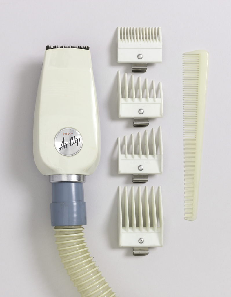 A plastic white hair clipper attached with a blue piece to a clear hose.