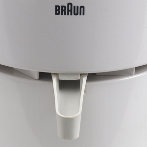 A white Braun juicer with a circular bottom and slightly larger circular top. A square metal handle comes from the lower section of the juicer and small circular opening on the top is covered by a light blue top.