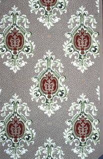 On gray ground with allover white and black specks, staggered  medallions composed of framed white scrolls, beaded frame and inside burgundy ground with lavender scroll motif.