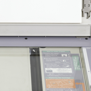 Off-white copier with a clear top and grey trim. The copier has an attached lid on back. Paper feeds on the right side.
