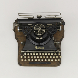 """Typewriter composed of a wooden body and metal elements. Inscribed on label, front: """"For All Nations and Tongues."""""""