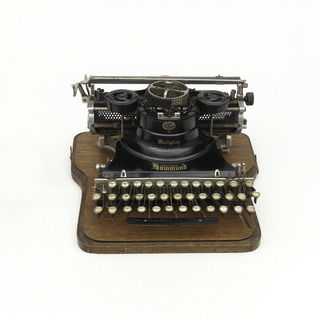 "Typewriter composed of a wooden body and metal elements. Inscribed on label, front: ""For All Nations and Tongues."""