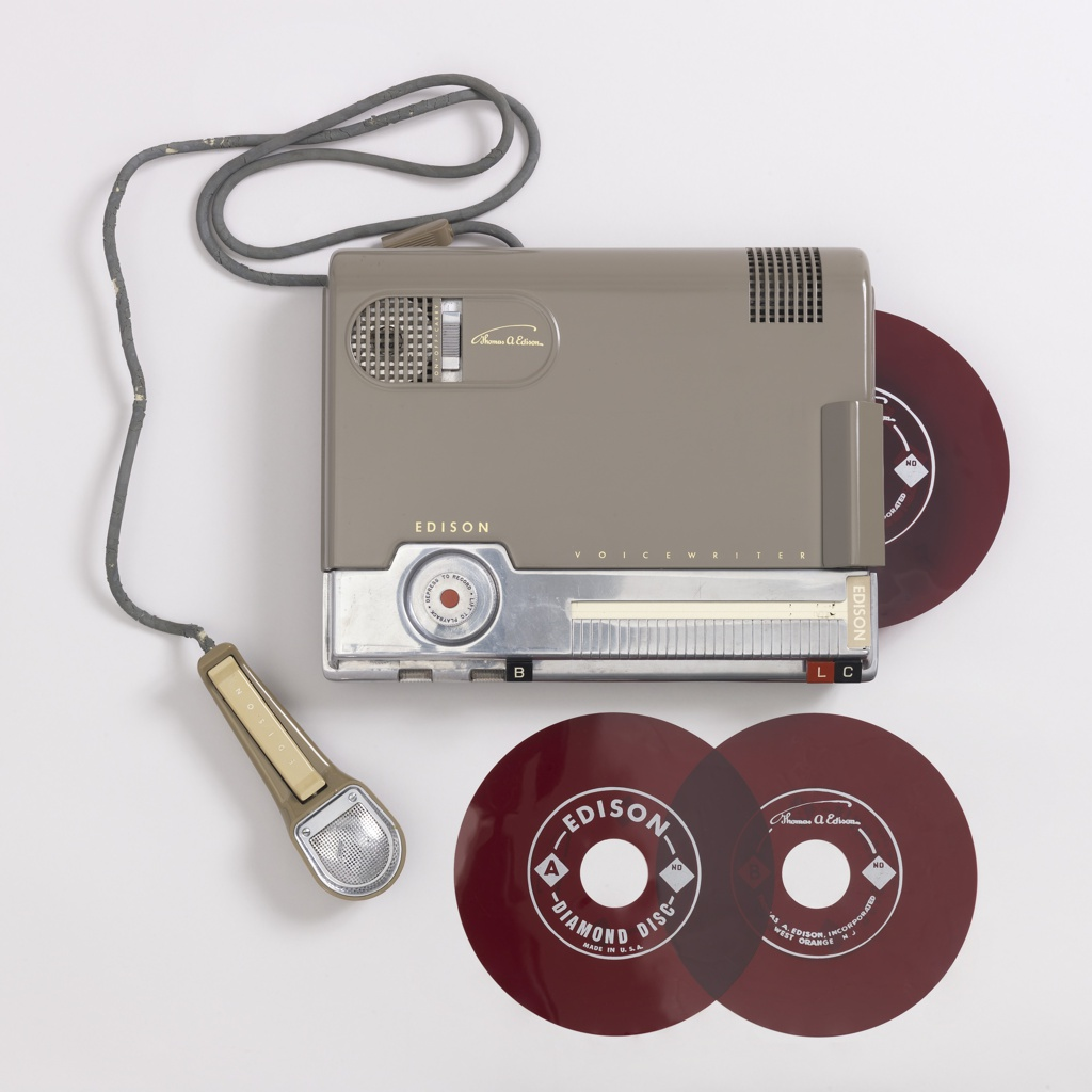"""Rectangular gray recorder with microphone attached by cord; disks. Recorder has controls in red, black, and metal with white text: """"B"""", """"L"""", and """"C"""". In relief: """"EDISON""""; """"VOICEWRITER""""; """"Thomas A. Edison""""."""