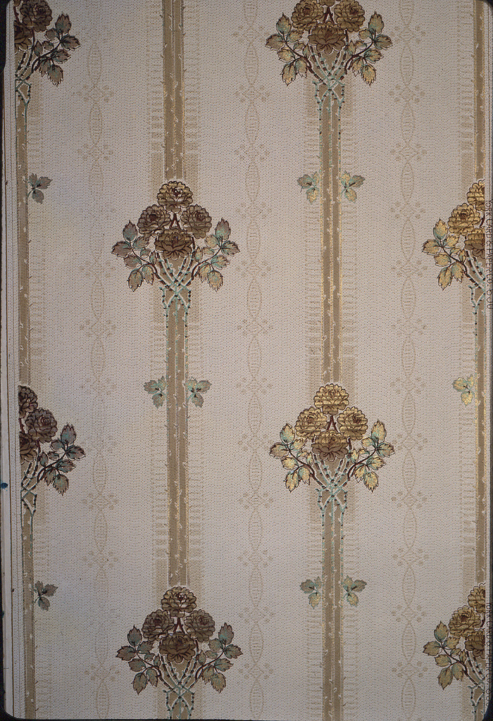 "Floral stripe design. Repeating motif of bouquet with four roses at top of ""v"" formation of rose foliage. The rose stems form the outside edges of the stripe. A pair of leaves appears on either side of the stripe mid way between to bouquets. Printed in metallic gold and green pigments and brown on tan background."