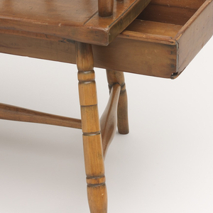Small comb-back of five spindles.  Right arm terminating in  large ovate writing surface supported by two turned braces and covered with red leather; left arm is knuckled.  Arm assembly rests on two turned seventeen spindles.  Broad slightly dished seat supported by four turned legs joined by H system of turned stretchers; drawers under writing arm and seat.