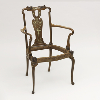 The crest rail is round eared with carved scrolls at center.  The seat is characterized by a serpentine front, on thin cabriole legs that terminate in padded slipper feet.  The splat is pierced towards the top of the chair, and inlaid with ivory scrolls, fish, ribbons, and torches.  An outline of inlaid ivory appears on the seat's frame and arm rests, as well.  The chair also has inlaid scrolls and dots on the knees of each front leg.
