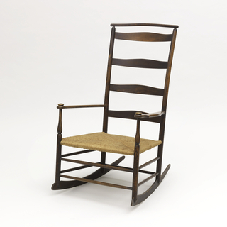 Slat back armchair with arms and a cushion rail; back consists of four oblong slats; seven turned stretchers between legs; two at front, left and right, one in rear; simple arms on turned front stiles topped by flat knobs.