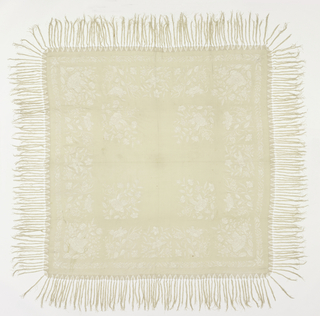Large square shawl of white silk fringed on all sides with white silk. Embroidered around border and in four corners with white silk thread in realistic floral design.