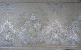 Floral bouquets, alternating large and small, set within scrolling framework. Printed in grisaille, metallic gold and mica on a tan ground. Rococo style design.