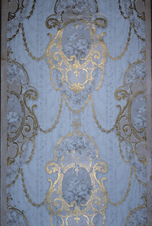 Floral bouquet in medallion. Medallions are connected by swags. Printed in metallic gold and grisaille on a ribbon-stripe or moire blue-gray background.