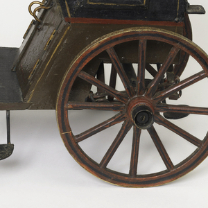 A one-horse Hansom carriage model, the cabin with one wheel on each side supporting an enclosed seating area, with a window on each side, the roof with a luggage rack and hand hold, all behind a platform accessible by a small step with front guard wall with two curved bars to connect to a horse's harness, and with carriage lamps on the side.