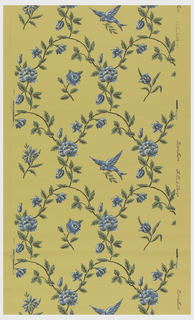 Diaper pattern created with vining floral motif. Blue birds and floral sprigs alternate within this framework. Printed in blue and green on a yellow ground.