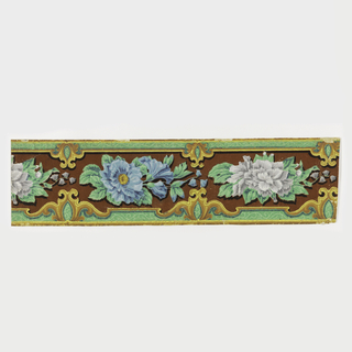 Rococo moldings decorate the upper and lower edgings; enclosed between them, with a flocked background is a frieze of flowers of alternating colors; printed in yellow, gold, blues, greens, with a rust and dark brown flocked background.  H# 555