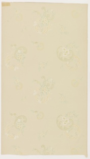 Round scrolling acanthus scrolls with attached floral sprigs, alternates with smaller versions of same. Very open design. Printed in yellow, light blue, and tan on light colored ground.