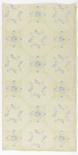 Circle or wreath of blue flowers with intertwined stems, printed in circular void. A quatrefoil or four-pointed star motif, with floral fill, sits at the juncture where circles meet. Printed in blue, green, and tan on light tan ground.