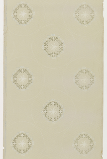 Round foliate medallion having a lacy effect contains a brown inner ring of acanthus scrolls with a blue outer ring. Each medallion is enclosed within a dotted circle. Printed on a tan ground.