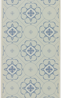 Quatrefoil or tudor rose shape, composed of blue scrolling foliage. Set within a square with a circle set into each corner. Printed on a light blue ground.