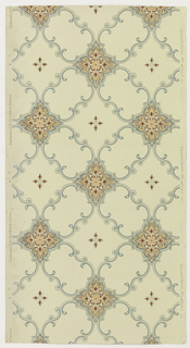 Geometric pattern in grid format formed of foliate scrolls with dotted fill. Intersections oare filled with quatrefoil motif. Floral motifs in every second grid. Printed in terra cotta, red, and blue on off-white ground.