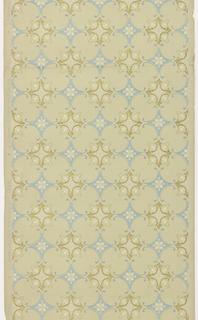 Geometric pattern resembling tile work. Diamond-shaped blue motif alternates with a more round yellow ocher motif. Printed on tan ground.