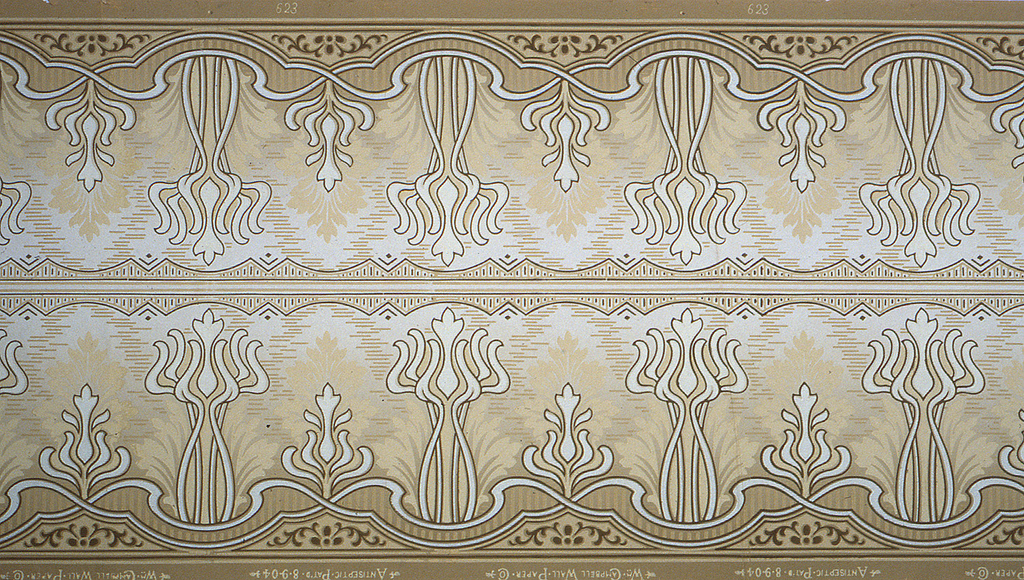 Art nouveau style with white bouquets of abstract vines on a tan, cream, and silver ground. Two borders printed across the width.