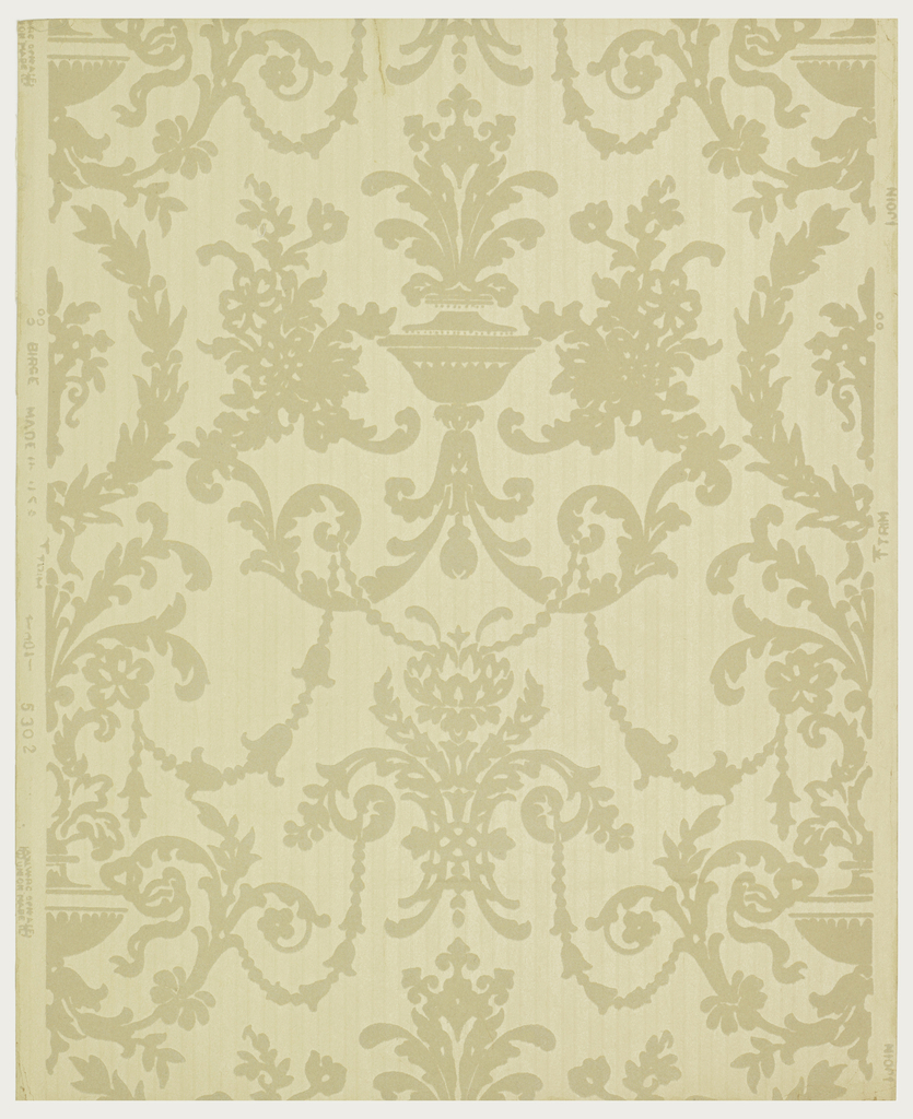 "Late 18th century French design. A symmetrical pattern composed of an urn with floriated foliage, with the usual festooned swags and acanthus leaf scrolls. The old ivory rayon flock design is on an embossed field which simulates a striped moire silk combined with a twill stripe - both narrow. Printed in right selvedge: ""Birge Made in U.S.A. 5302 U.W.C. of N.A. Union Made."""