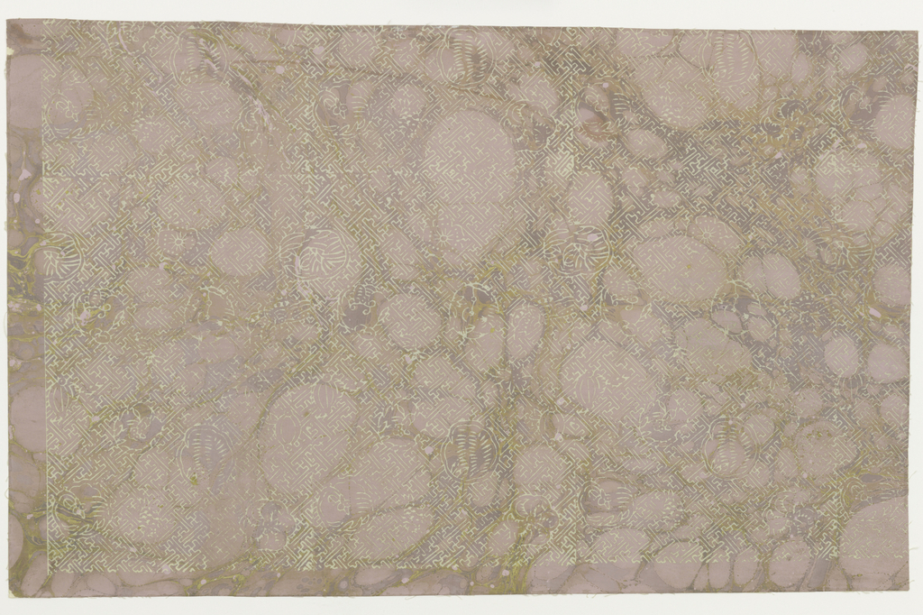 "White fret-work interspersed with white fruits and flowers irregularly spaced. All are in outline against a ""tortoise shell"" ground of lavender and gold. A non-repeating ""Chinese Tea Chest"" paper."