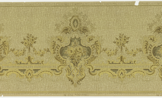 Frieze with rococo inspired, horizontal pattern. Large shields of roses and acanthus leaves are linked with floral garlands and swags of c and s scrolls. An allover hatched pattern gives the panel is printed beneath the floral elements, giving the panel a woven appearance. The design is printed in shades of beige, brown and olive green on a tan background.