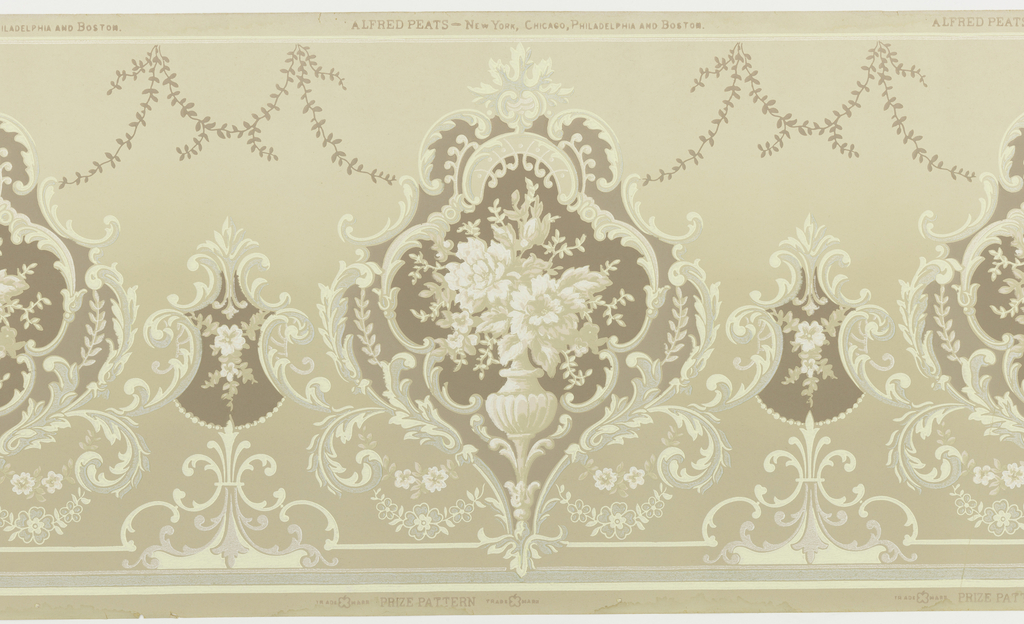 A repeating pattern of acanthus cartouches containing a vase of flowers upon a pedestal joined to complementary cartouches on a ground of beige mat becomes darker towards the base with garlands of flowers and leaves bordered between horizontal bands. Printed in beige, brown, mica, white, pink, off-white and pale green.