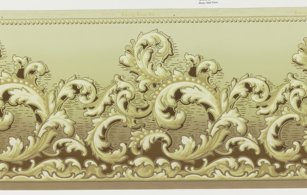 Rinceau motif in haphazard shapes. Bottom border edge wave molding with colors to look like a foamy sea. Top border edge of beaded motif shaded to look 3-dimensional. Printed in brown, white, gold, gilt, tan and greenish-yellow on green field.