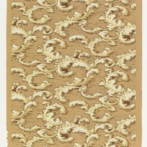 Scrolling acanthus leaves, the larger of which contain beading. Printed in monochrome off-white and tan on darker tan background.