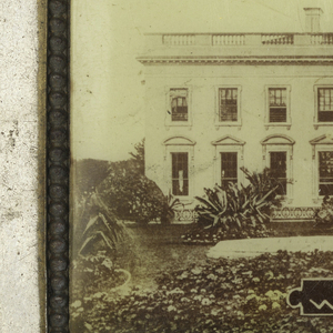 "Rectangular, curved top and bottom, featuring horizontal, sepia-toned, photographic image of the White House, inscribed below ""White House, Washington D.C."", reverse features horizontal, sepia-toned and hand colored photographic image of the Capital, inscribed below ""The Capital, Washington, D.C."", side panel beneath White House image inscribed ""Washington, D.C."" Lid hinged on side. Striker on bottom."