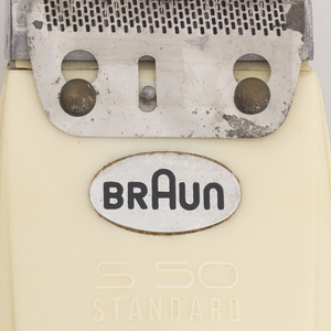 Oblong, off-white, plastic body with grooves; perforated, metal, razor attachment at top; switch on reverse, element to plug in detatchable cord on bottom.