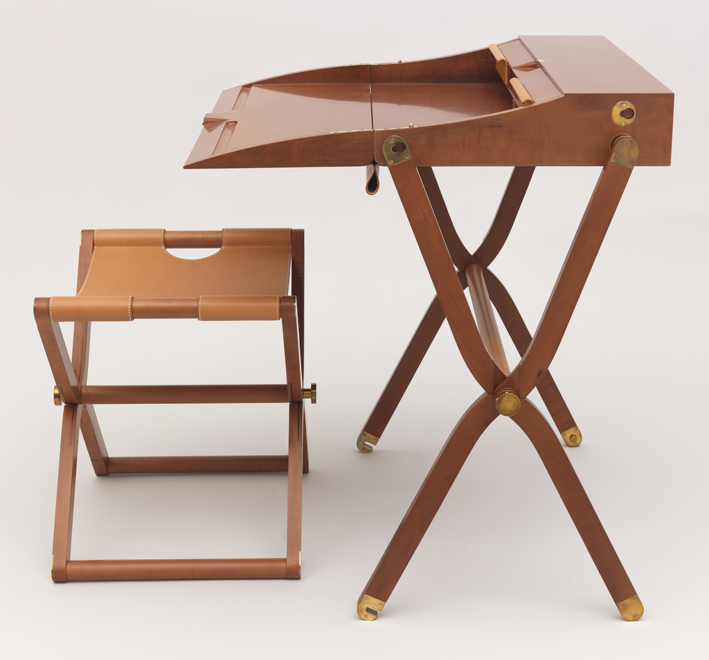 Folding desk with crossed hinged legs and brass hardware. Table has box-like top that slides close.