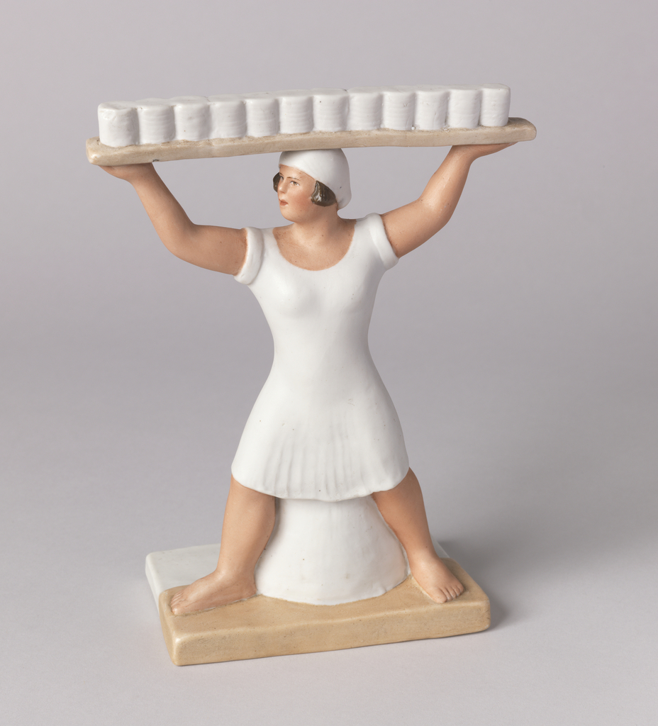 Woman standing, with legs spread, holding on top of her head a board with stacks of ceramic dishes; she wears white cap and dress; stands on rectangular base.
