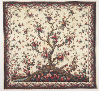 Mezzaro in a multicolored design on a white ground. Central large-scale tree with many different blossoms. Small flanking tree on either side. Floral sprays, insects, birds and animals scattered over the ground. Border of massed flowers and fruit with perching birds.