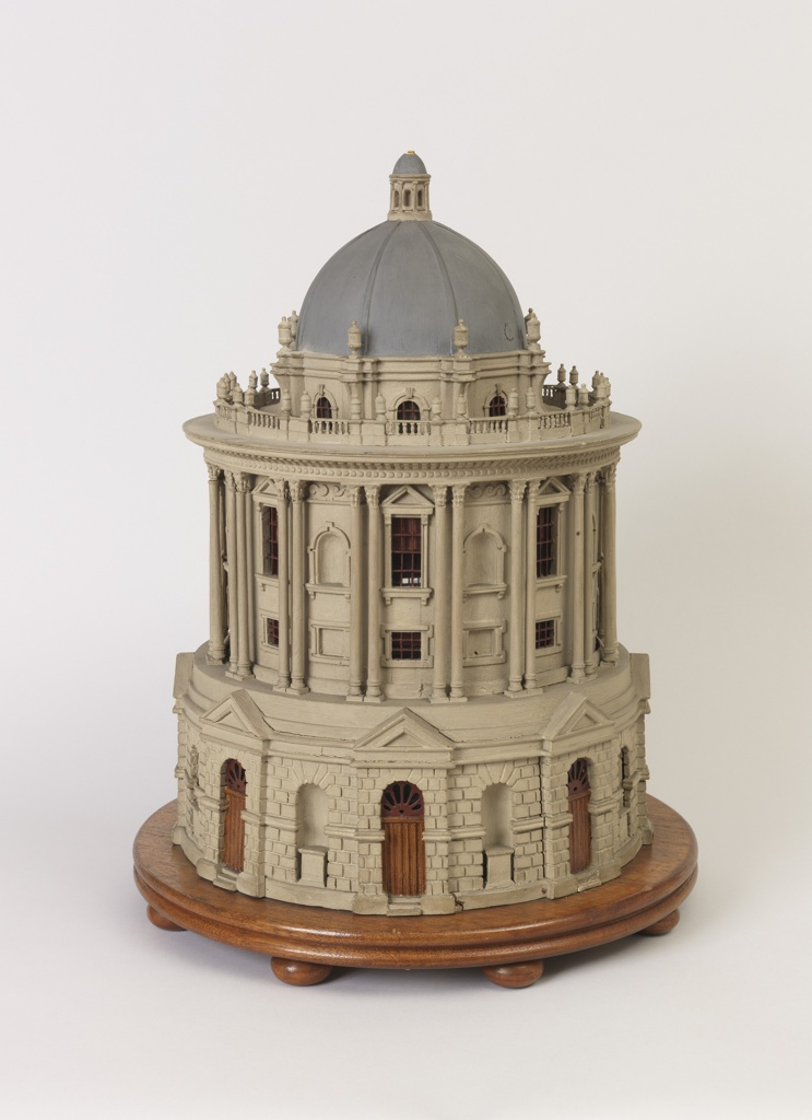 the circular building with rusticated lower tier supporting set back upper tier with double columns between window bays, alternating blind and paned windows, surmounted by a domed top with finials around and a spire above, all replicating the Radcliffe Camera building in Oxford England.