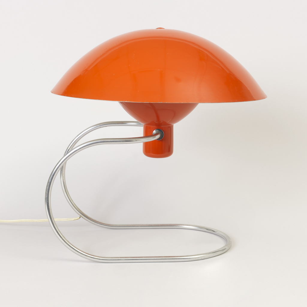 Orange, pivoting domed shade mounted on orange bulb housing with continous, curved tubular metal base.