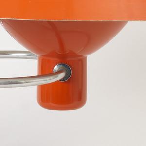 Orange, pivoting domed shade mounted on orange bulb housing with continous, curved tubular metal base.