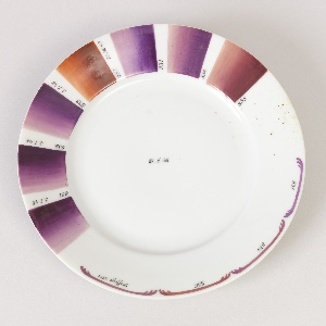 "the circular plate enameled with samples of varying shades of purple, mauve and russet, in rectangular patches with degrees of shading numbered 831-835 and with the date 3-I-48 on the side of each, on slightly over half the plate, and with samples of border decoration in the same colors and numbers, plus one labelled ""Staffage 1551"" on the remainder of the rim."